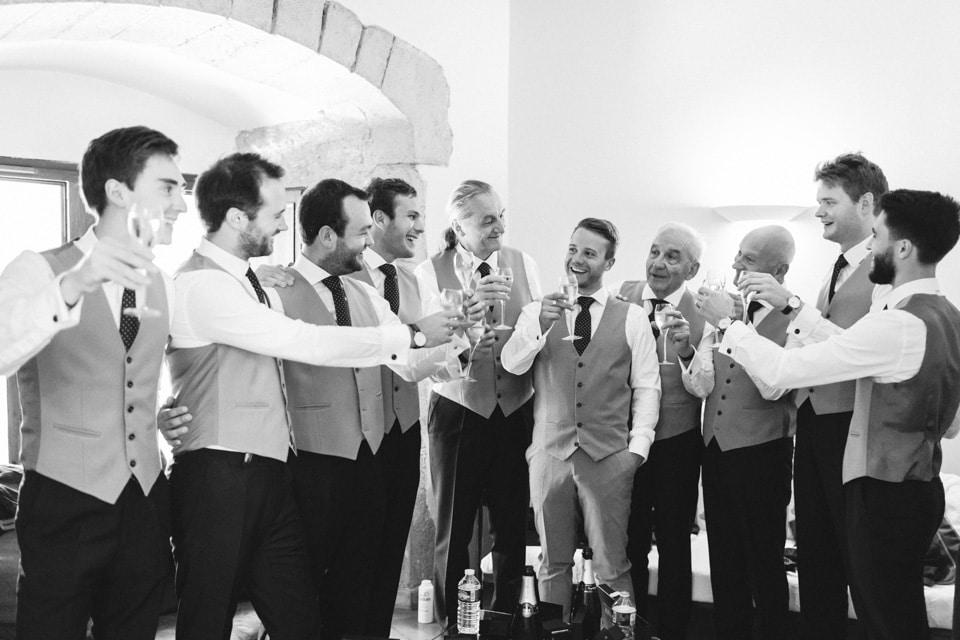 le marié et ses témoins boivent une coupe de champagne avant la cérémonie religieuse de mariage