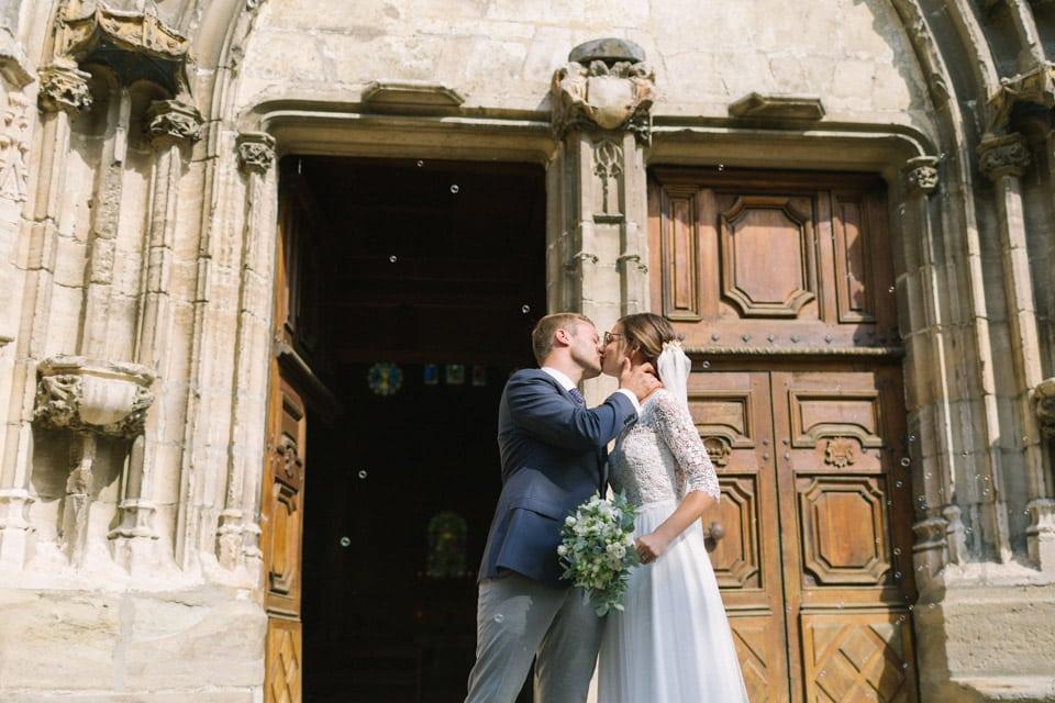 baiser des mariés devant l'église après leur mariage