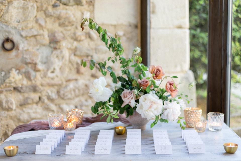 plan de table du mariage entouré de fleurs et de bougies