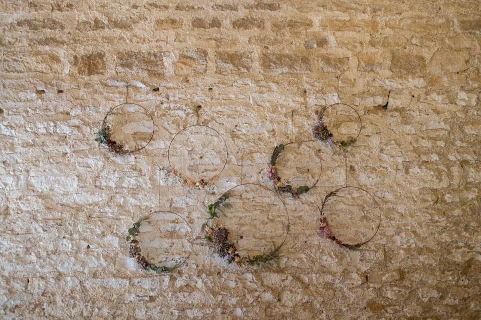 cercles ornés de fleurs séchées sur les murs de la grange du chateau de barbirey